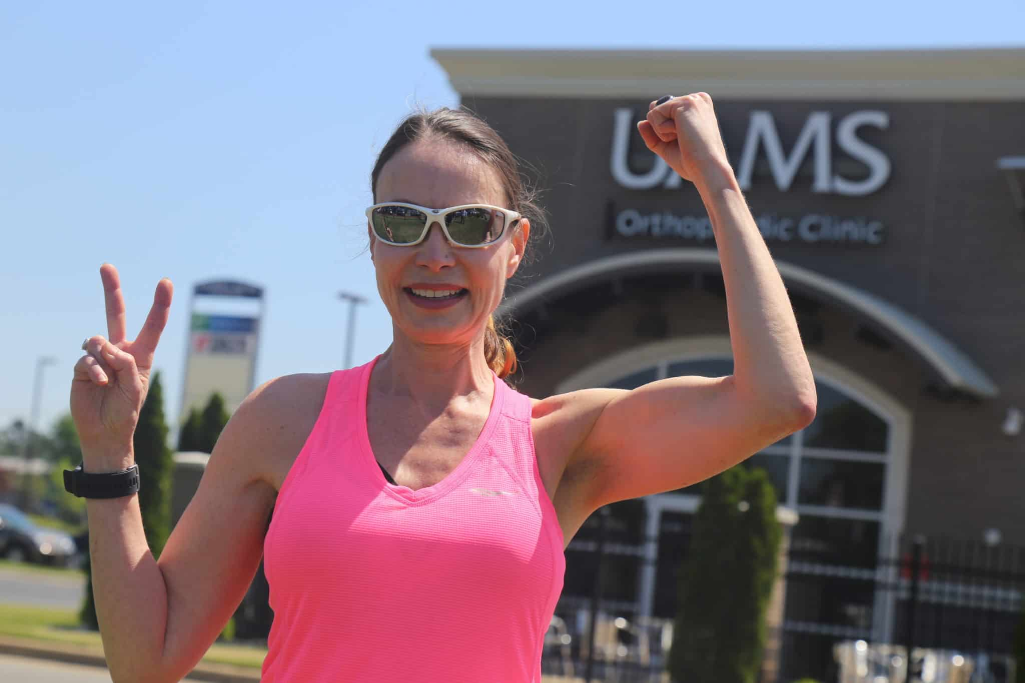 Mary Anne Hanson flexing outside UAMS ortho clinic